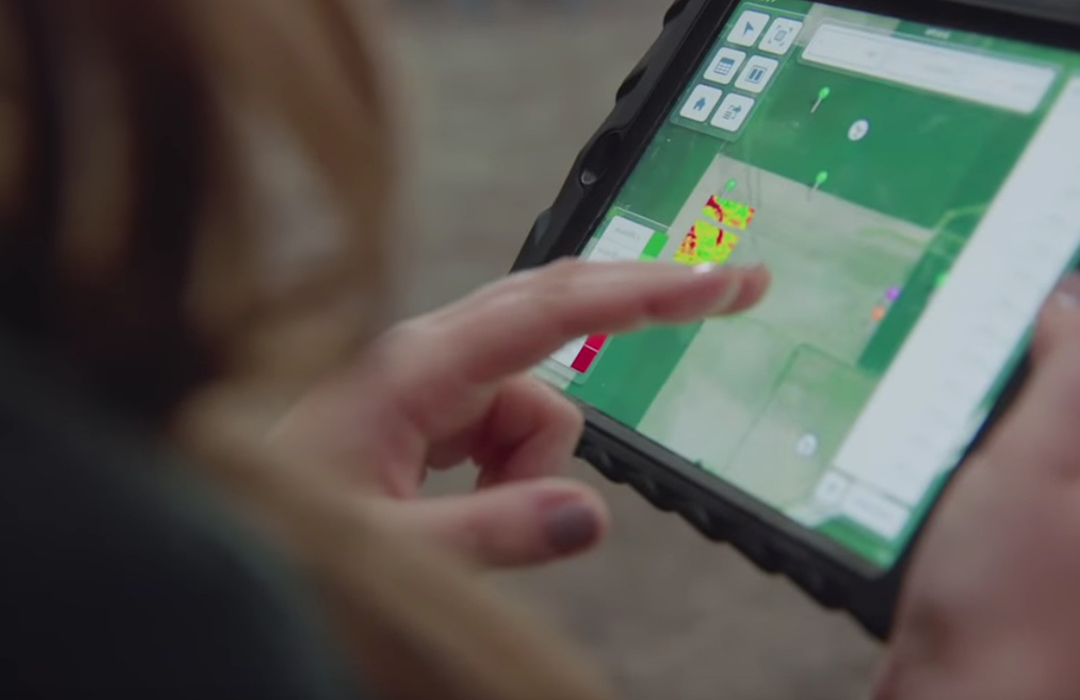 Asgrow® technical agronomist holding iPad with Climate Fieldview™ tool